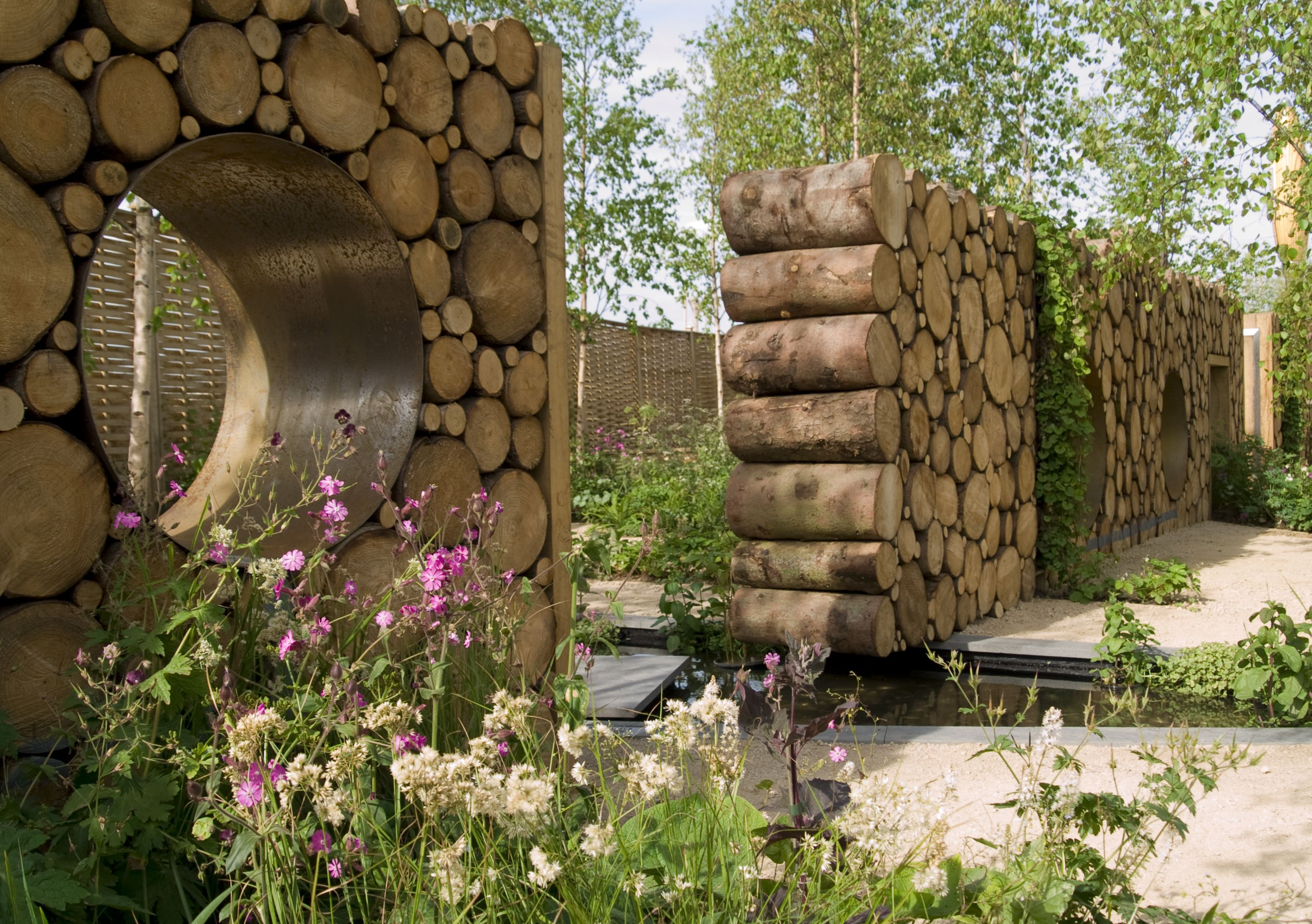Wood Log Wall In Garden With Eyelets