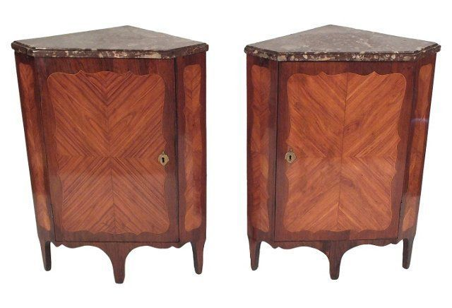 1870s French Corner Cabinets 1870s pair of French Louis XVI-style corner cabinets with rich beveled-marble tops. Cabinets have inlaid veneer doors and sides, brass keyholes, and two wood shelves inside. Wood finish is a lovely combination of rouge, mahogany, and cherry.