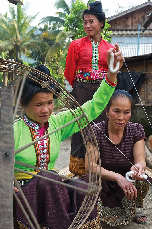 Laos, textile weaving: Tai Lue woman from Ban Na Nyang teaches spinning cotton to a Tai Dam woman from Phongsaly, 2010. Photograph by Jack Parsons. Museum of International Folk Art, Santa Fe, New Mexico