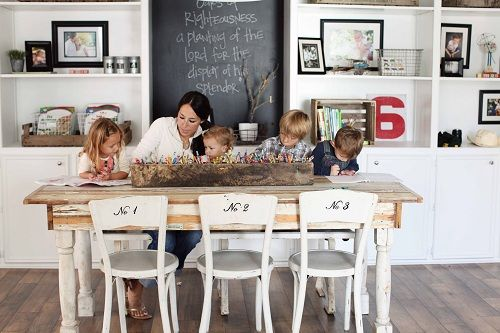 rustic dining table and antique wooden vessel filled to the brim with colored pencils, crayons, etc! love!