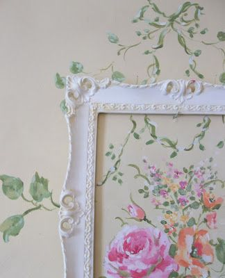 Delicately painted flowers on wall, with an empty, white frame placed over top. Lovely how the leaves stretch beyond the frame's edge / Napoleon's Notes