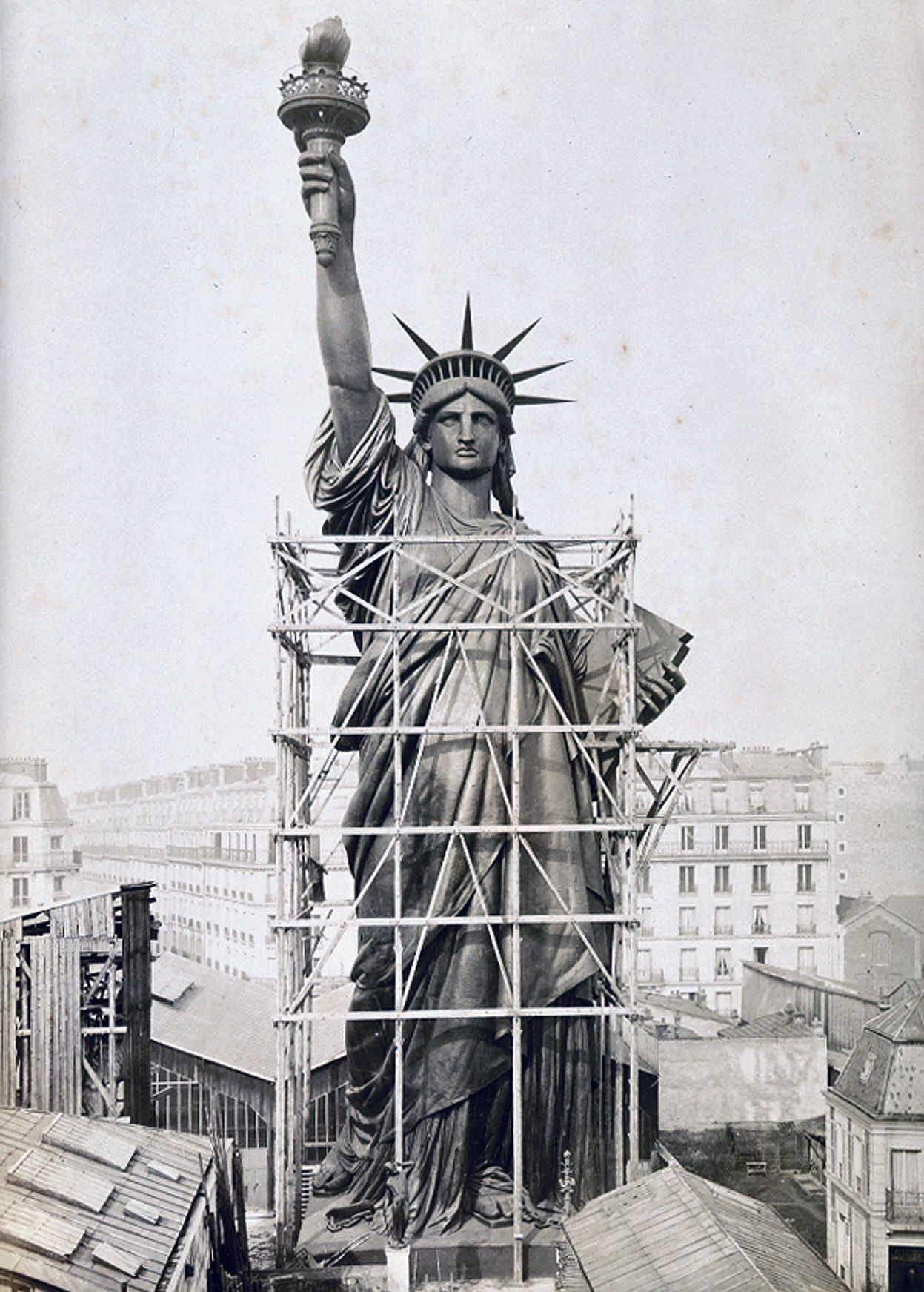 The statue of liberty surrounded by scaffolding as workers complete the final stages of construction in paris what a lady