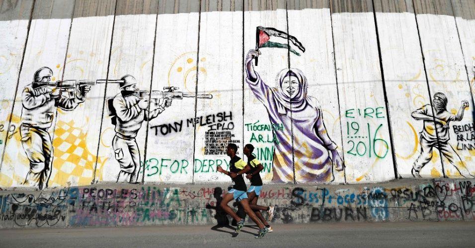 20160401 -  Participantes correm ao lado da muralha israelense que divide a cidade de Belém, na Cisjordânia ocupada, durante a 4ª maratona da Palestina Imagem: Thomas Coex/AFP