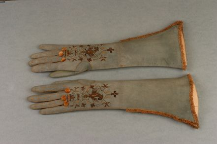 A pair of women's elbow length gloves circa 1685 – 1700, of white doeskin leather stained green now faded to blue, flesh side out, the back of hand and fingers embroidered in pink silk and silver thread in a stylised floral design encompassing raised work silver phoenix, three pink silk rosettes to the knuckles, decorative pink silk embroidered flecks and edging to the fingers, edged in pink silk fringing.