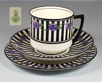 Doulton deco: unnamed tea trio by Robert Allen, E9697, RA8264B, c1927 (backstamp). Purple violets and green leafy, thorned vine on black and white striped border with black highlights and trim.