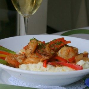 Photo of local shrimp, smoked sausage, bell peppers, stone ground grits, tasso ham gravy