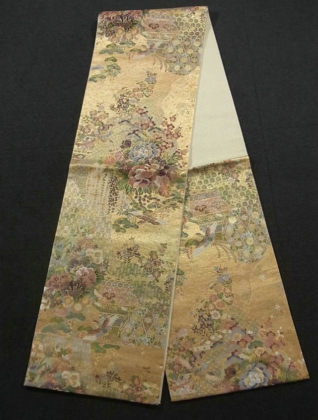 This is a glamorous Fukuro obi with classical pattern on 'michinaga-dori'(wavy line), which is woven. It also has 'zuicho'(auspicious bird with long tail) and seasonal flower such as 'kiku'(chrysanthemum), 'botan' (peony), iris and 'kaede'(maple leaf) pattern on the gold background.