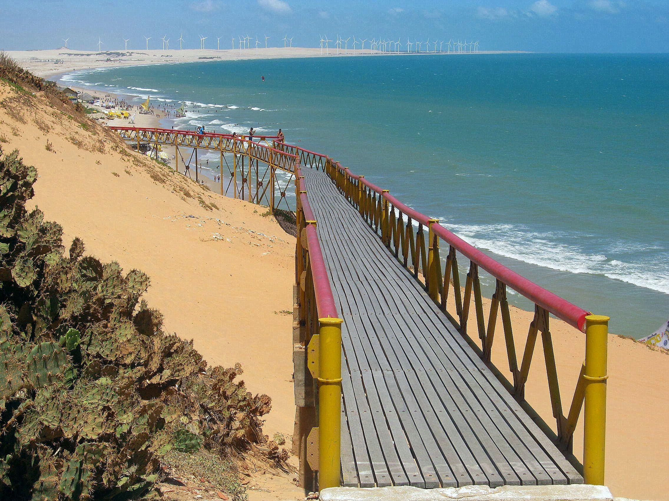 Ponte na beira da praia e os geradores de energia eólica ao fundo, Canoa Quebrada.