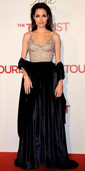 in an Atelier Versace black velvet gown with a plunging crystal-embellished bodice and Tiffany & Co. jewelry