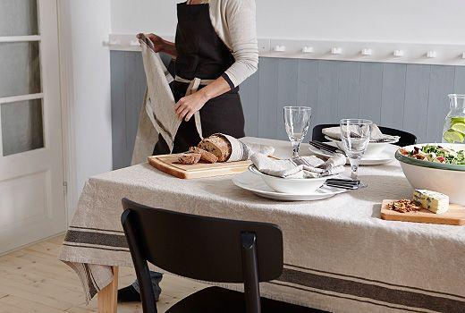 An IKEA VARDAGEN Tablecloth Set At A Dining Table And Someone Wearing A  Black VARDAGEN Apron