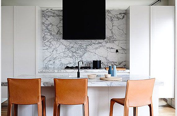KITCHEN DESIGN IDEA: Marble splashbacks. Melbourne-based firm Hecker Guthrie is a multi-disciplinary practice headed by Paul Hecker and Hamish Guthrie. Their work is driven by the principles of authenticity, consideration and enthusiasm, as is evident in this Malvern residence. A striking black rangehood matches the black tapware and accessories while the tan leather of the stools softens the room.