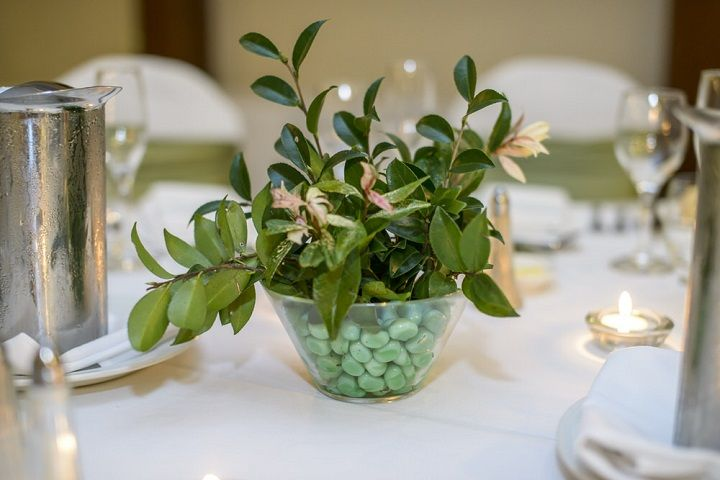 Glass bowl wedding centerpiece was filled in green stones + added some colourful plants