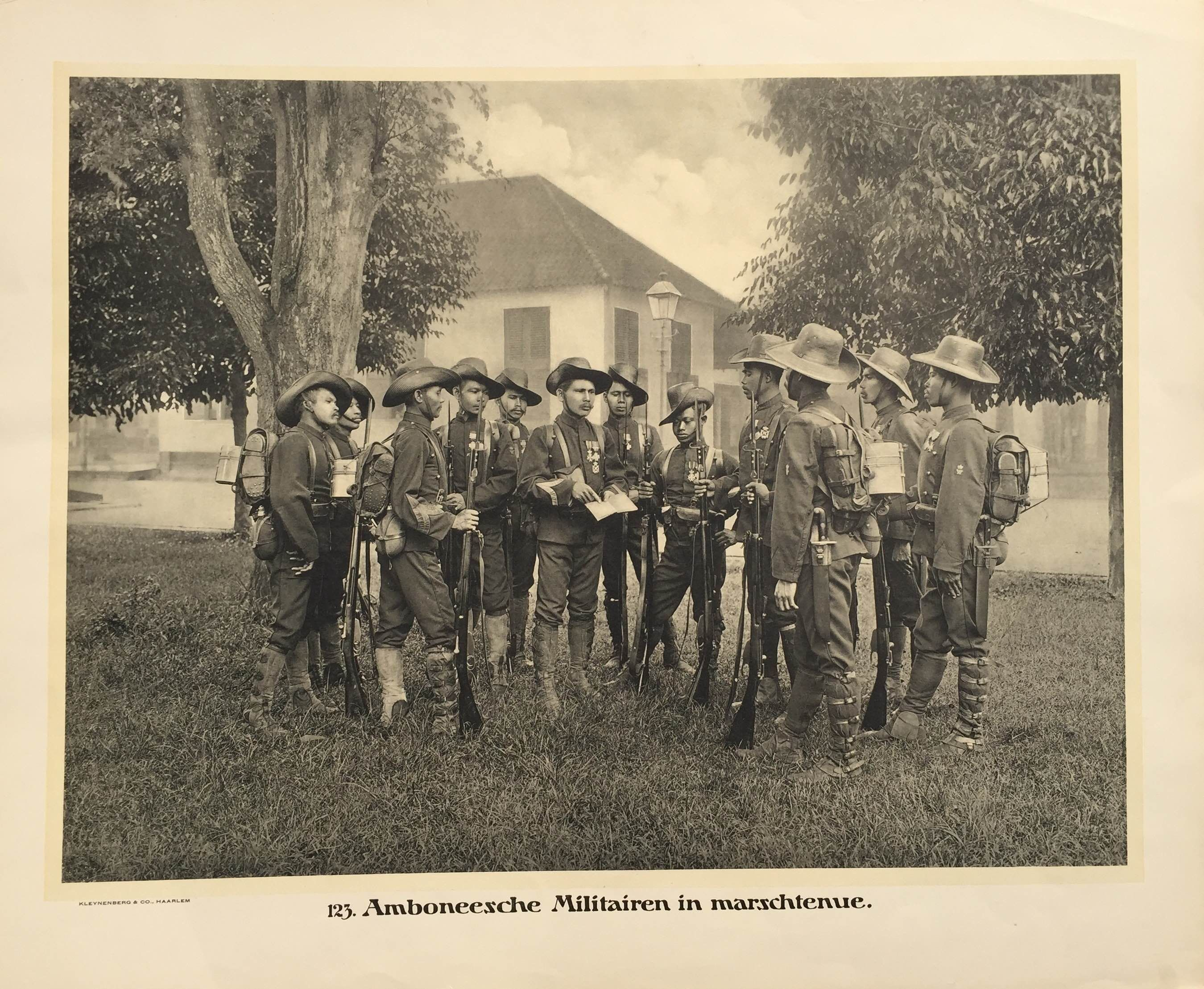 123. Amboneesche Militairen in marshtenue. Antique school board of Ambonese soldiers in marching tunics. Taken c.1895 and published between 1912 and 1914 in Holland. Ambonese soldiers, shown in this plate wearing their marching tunics, were...
