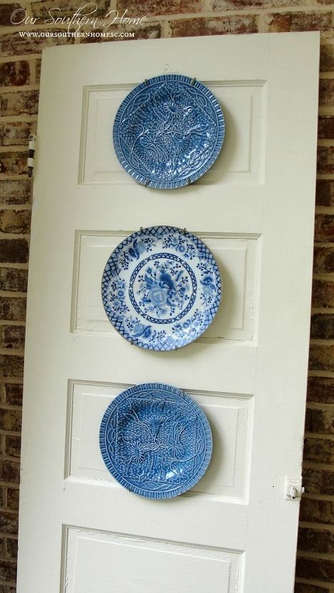 Thrift Store Door Plate Display #plateracks I took an old $4 thrift store door and simply leaned it against the porch brick wall. I have intentions of painting a porch rules sign on it, but for now it is functioning as a plate rack! I'm kind of liking it like this. I already had the plates on hand so this was a super cheap project!!! #bestofmay #summer #HomeAccessories #plateracks