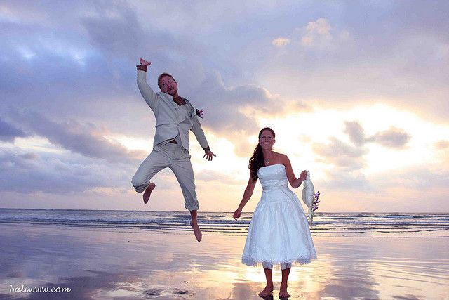 Plan your beach wedding a little before sunset to get the best pictures. Newlyweds at sunset on the beach