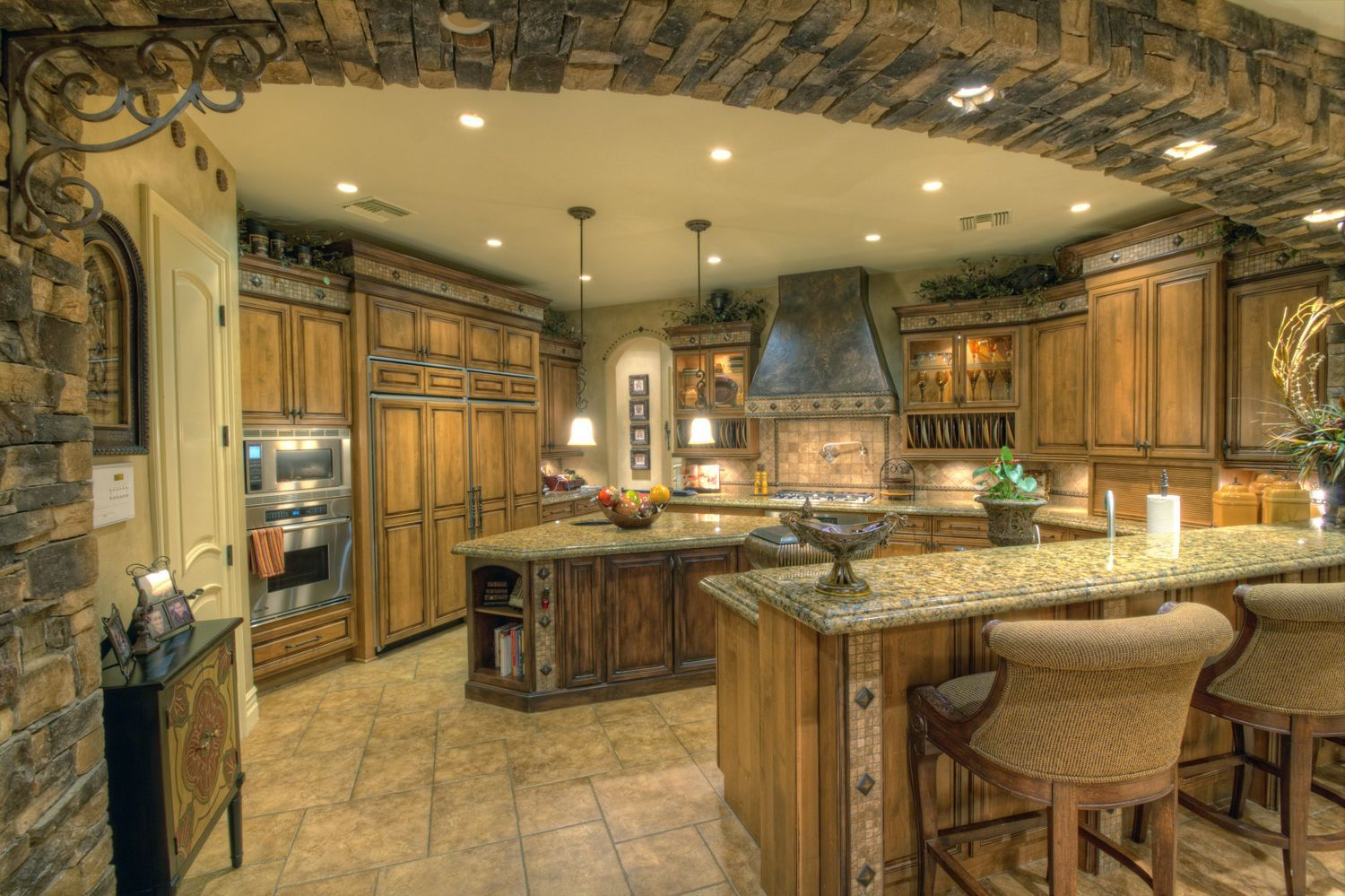 Luxury kitchen with stone archway and granite counter tops for Luxury kitchen cabinets
