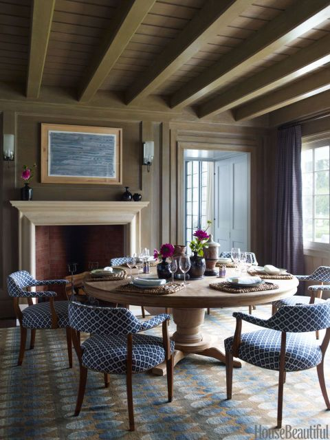 Designer Steven Gambrel paired grandiose appointments with unexpected colors (like cantaloupe!) in this Hamptons escape. A pedestal table from Ma(i)sonry is the centerpiece in the oak-paneled dining room.