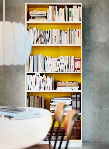 Librería blanca con fondo amarillo llena de libros.  5c23048d8dc6