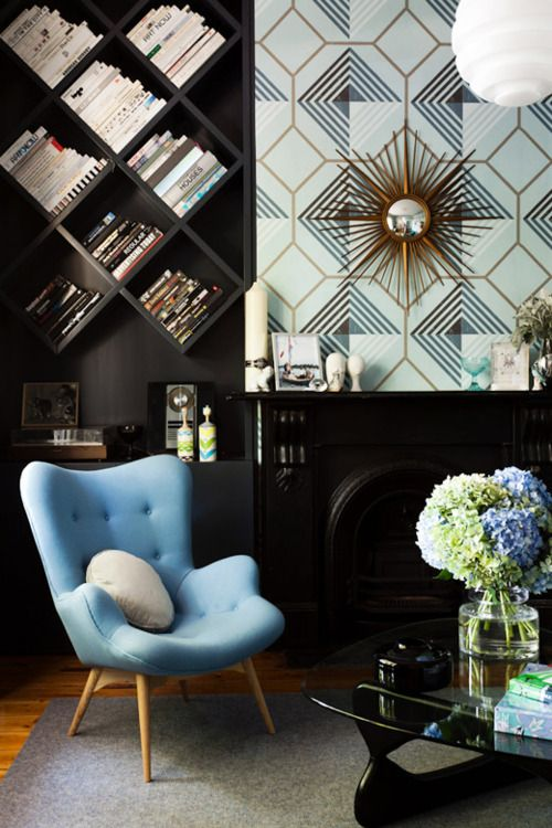 I love the black and white background with the pop of blue. I'm especially in love with the way the diagonal shelves were designed to perfectly align with, and repeat the geometric design in the wallpaper. Great job!