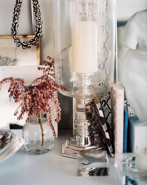 Decor - A hurricane lamp and a vase of flowers on a white surface
