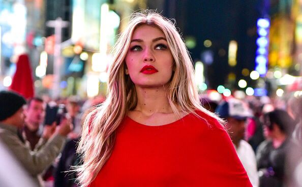 Gigi Hadid with bright red lips and matching dress - city lights - celebrity street style