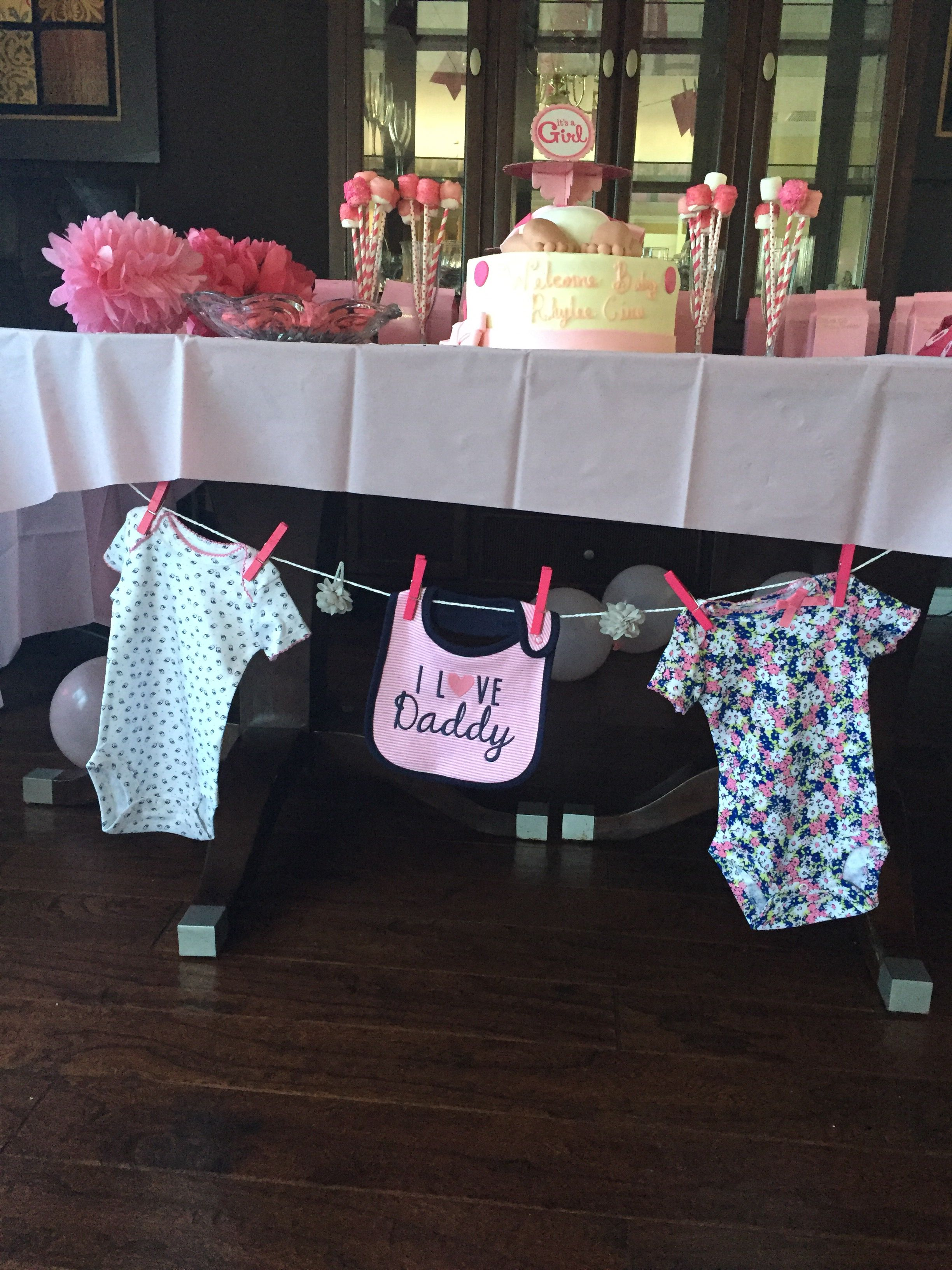 Baby clothes from Target clothes line with pink clothes pins for