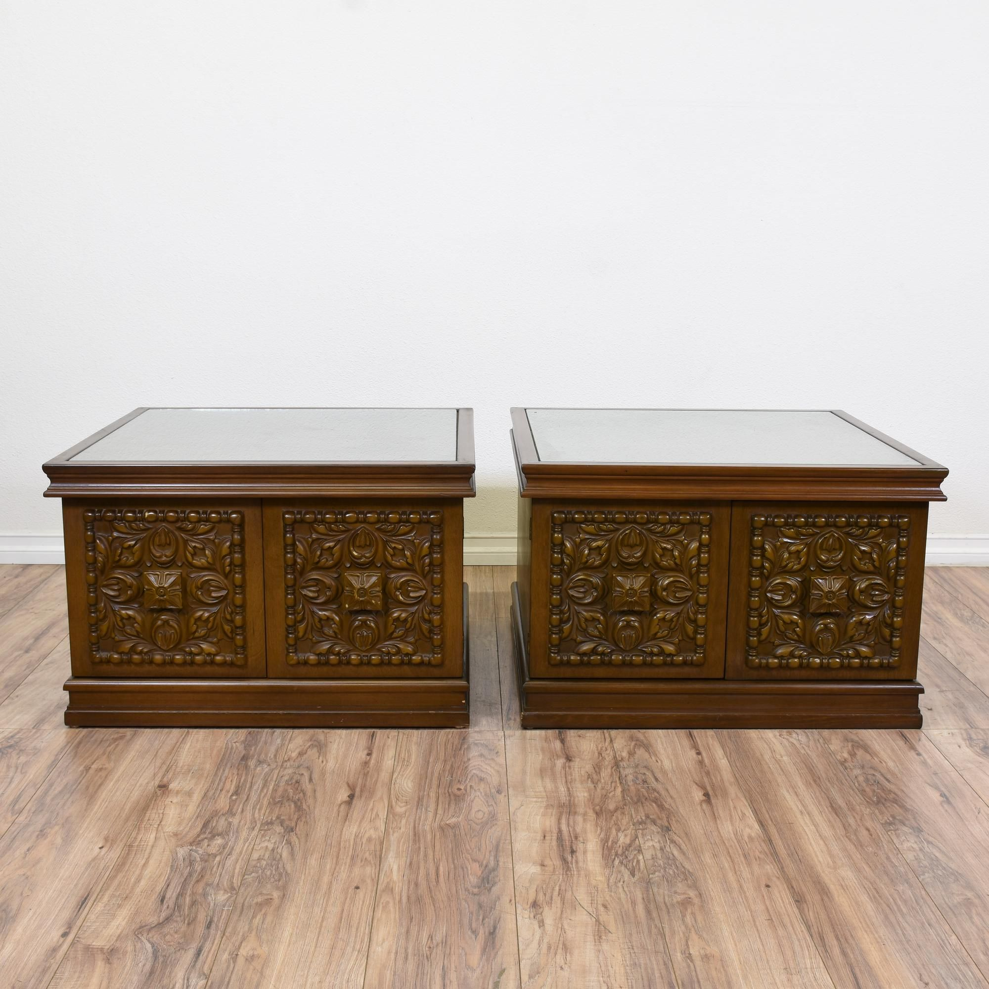 This pair of cabinet end tables are featured in a solid wood with a glossy walnut finish. These side tables are in good condition with square glass table tops, 2 intricate carved doors and a large interior cabinet. Perfect as nightstands with plenty of storage! #americanmidcentury #tables #endtable #sandiegovintage #vintagefurniture