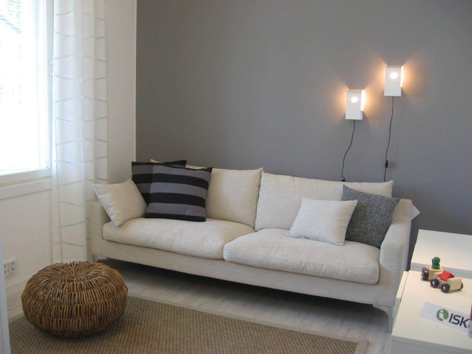 harmaa seinä ja valkoinen sohva..