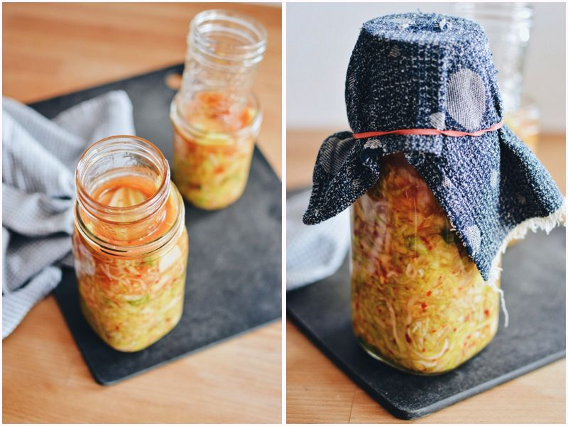 Kimchi kraut weighted down with small jar and covered with cloth.