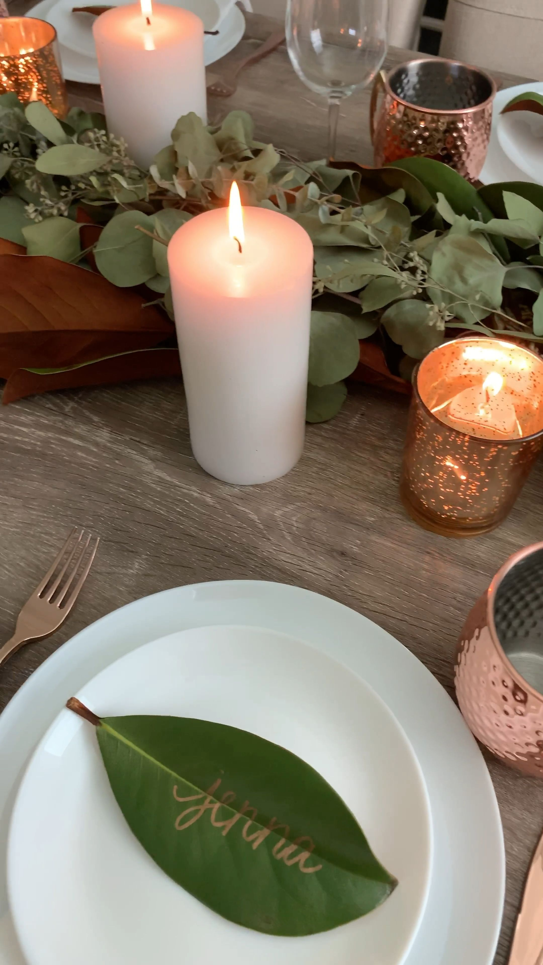 The perfect table setting for fall and winter! Features a diy fresh eucalyptus table runner, magnolia leaves and place cards and beautiful copper accents. #tablescape #eucalyptus #falldecor #tablesettings