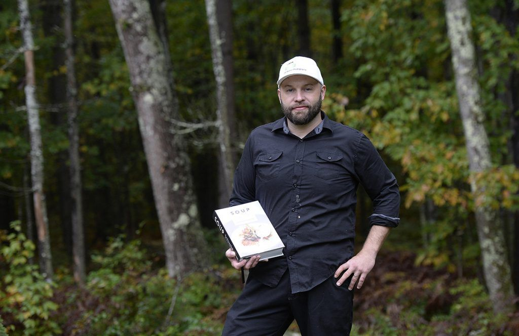 Derek of db maine photography holds his book