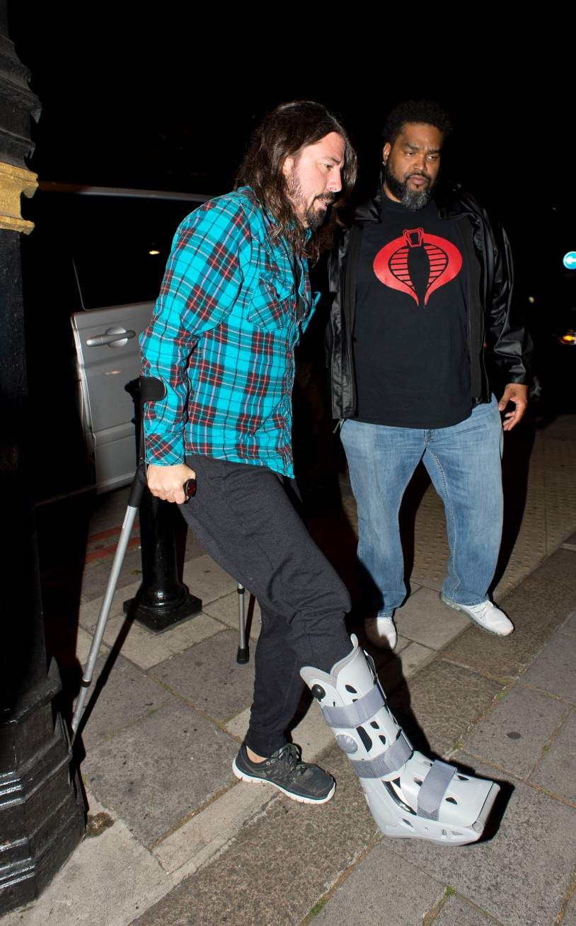 "Dave Grohl of the Foo Fighters on crutches and wearing an orthopedic walking boot after breaking his fibula. His description: ""like an old pair of take out chopsticks."""