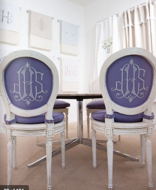 Monogrammed upholstered purple dining room chairs against white