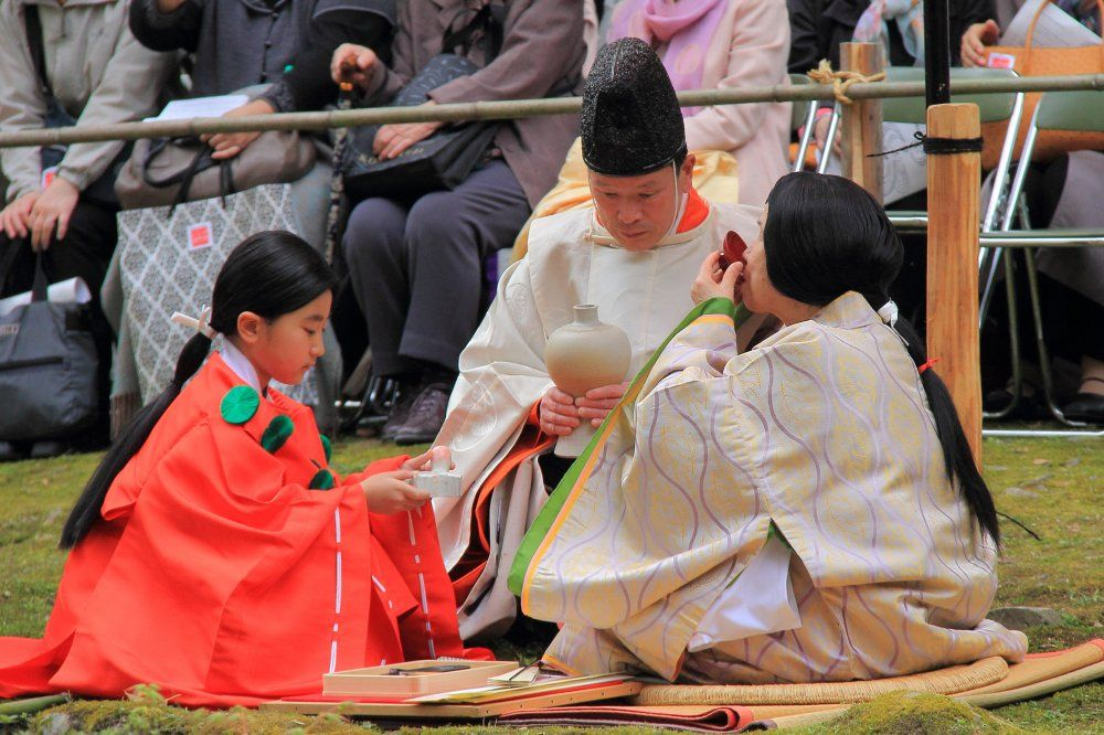 A man, woman and boy dressed in heian robes at a gokusui no en.