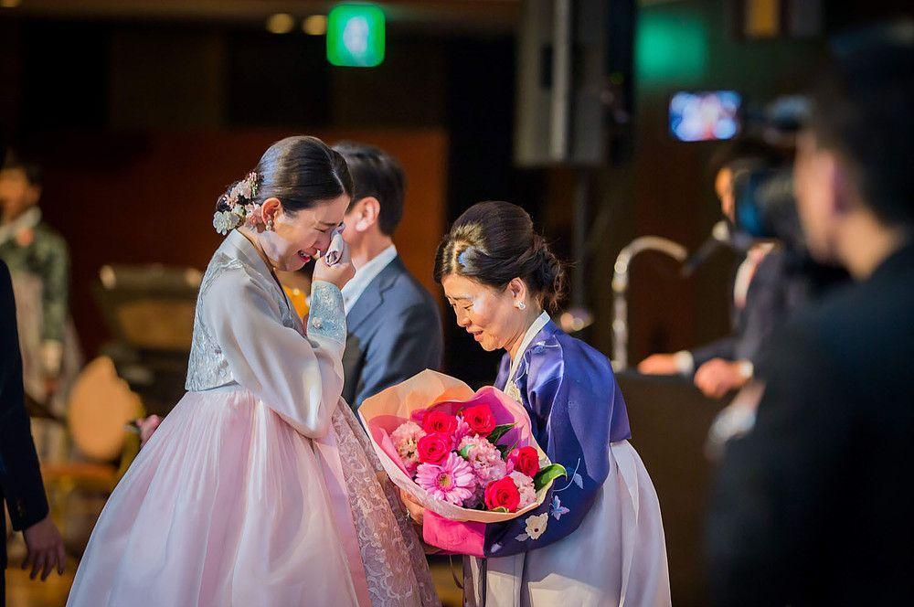 高輪貴賓館での結婚式で両親への手紙を読んだ後 花束贈呈中に想いが込み上げ涙する新婦とお母さん ウエディングフォト 結婚式 写真 韓国の結婚式