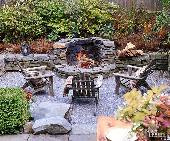 A cozy, sunken seating area becomes prime real estate for a fire pit. This fire pit is built into the stone wall for a truly custom, incorporated look. Three chairs offer the perfect spot for casual conversations on cool evenings.