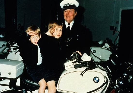 1987-10-27 William and Harry are taught to salute by Police Constable Ken Brown during a visit to the Headquarters of the Metropolitan Police Special Escort Group in Barnes, London
