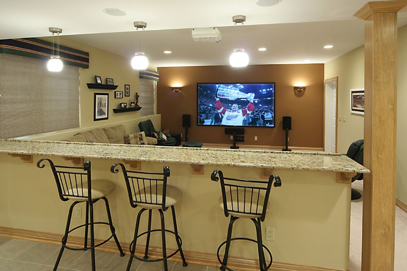 Sectional Couch With Bar Stools Behind A Half Wall Capped With Granite Bar  Top Doubles The