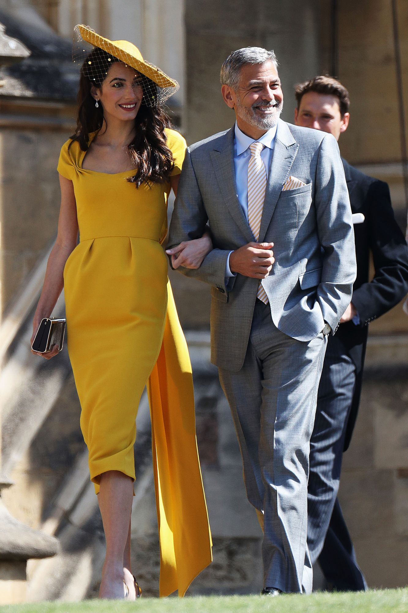 3bcd6217ec37a Amal Clooney stunned in a Stella McCartney marigold dress with matching hat  as George opted for a light grey suit. Shop the look  Carolina Herrera  dress