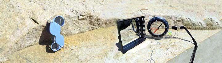 Une loupe de géologue avec double optique 10x et 20x ainsi qu'une boussole avec clinomètre intégré.