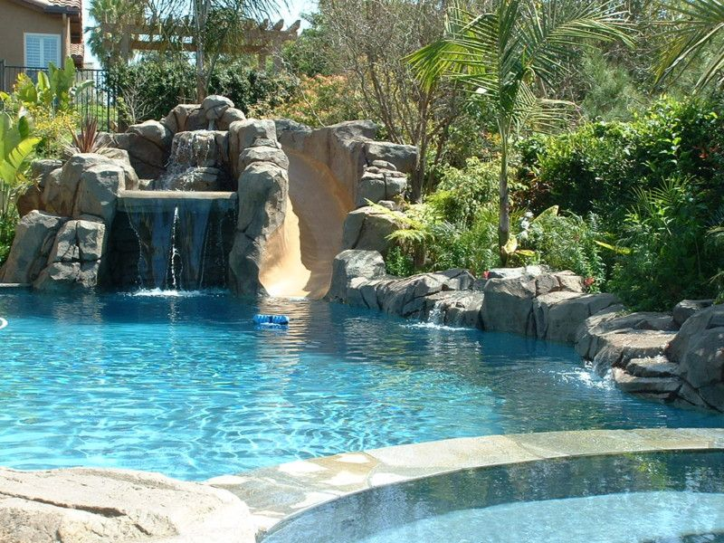 artificial rock water slide and grotto with jumping rocks and waterfall rock boulder coping on back pool wall