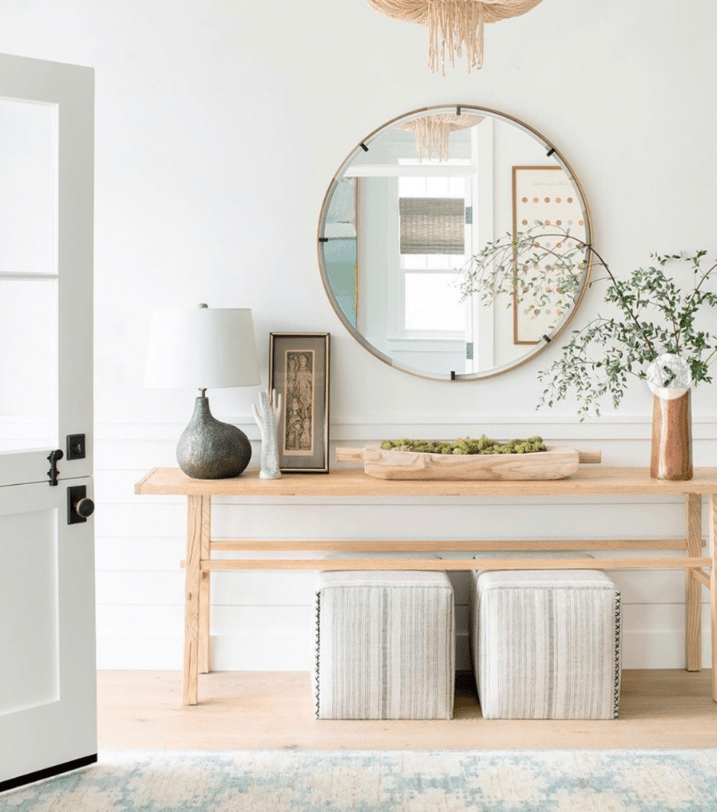 Entry console table decor ideas for your foyer. White trim work with a light wood table, round mirror, and matching lamps to decorate entryway. #consoletabledecorating #consoletableentryway