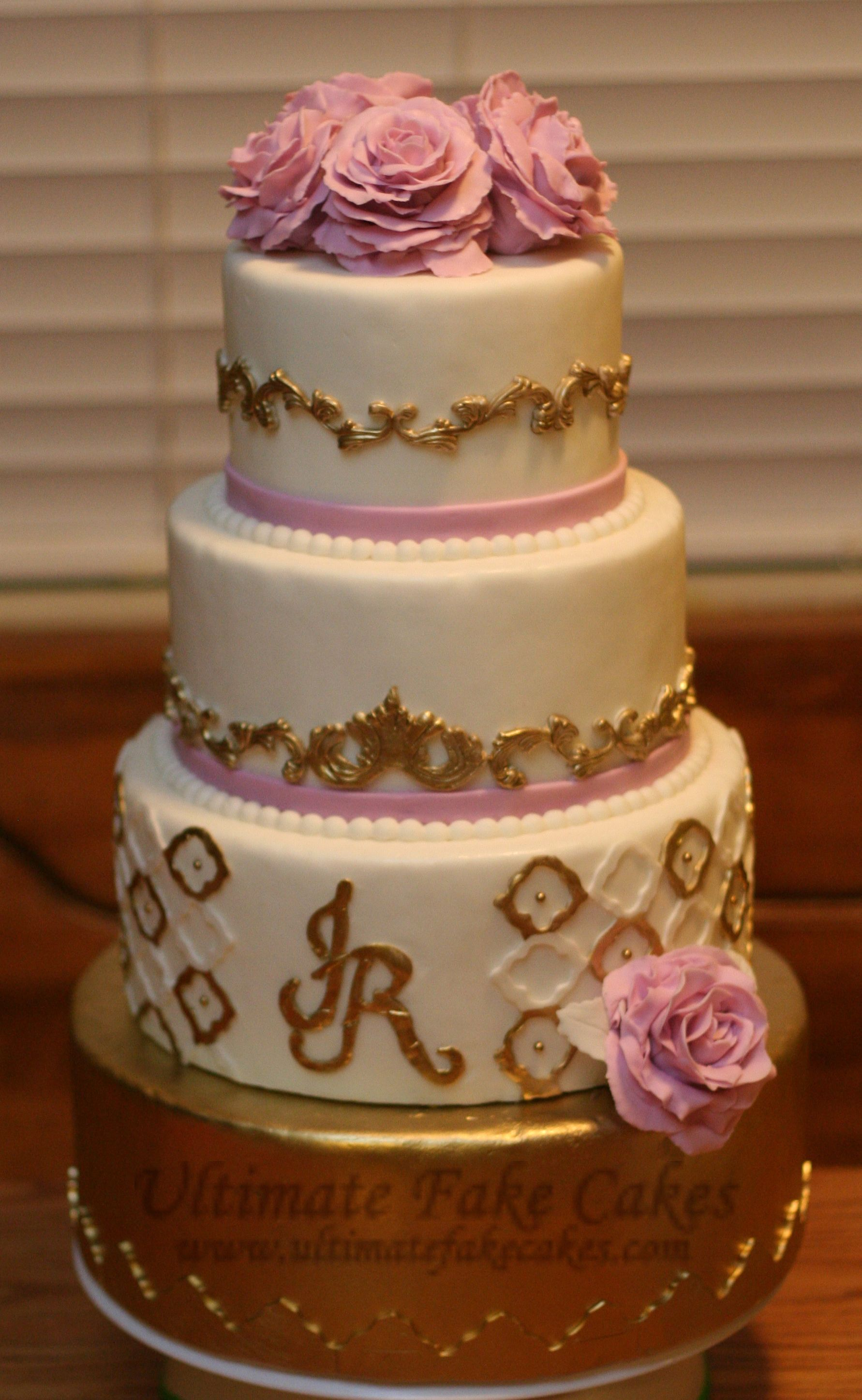 4-Tier Gold scrolling with peonies adoring the top. www.ultimatefakecakes.com