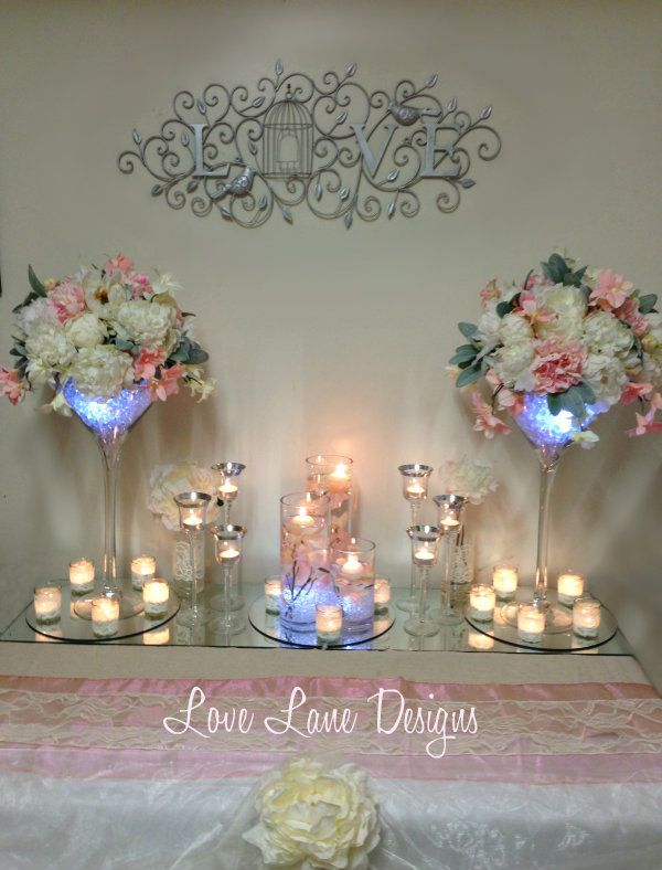 Peony floral arrangements with LED lights in martini vases, pale pink orchids, floating candles and tealights - Wedding expo set up