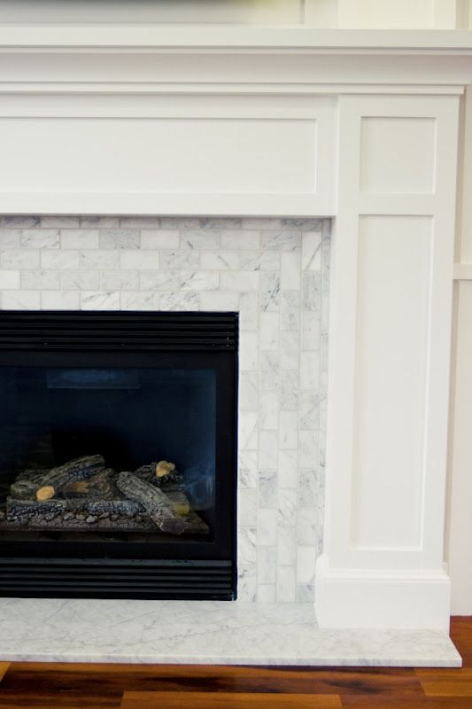 Carrara Marble hearth with Carrara Marble tile on fireplace. I love the way they changed direction on the running bond pattern.