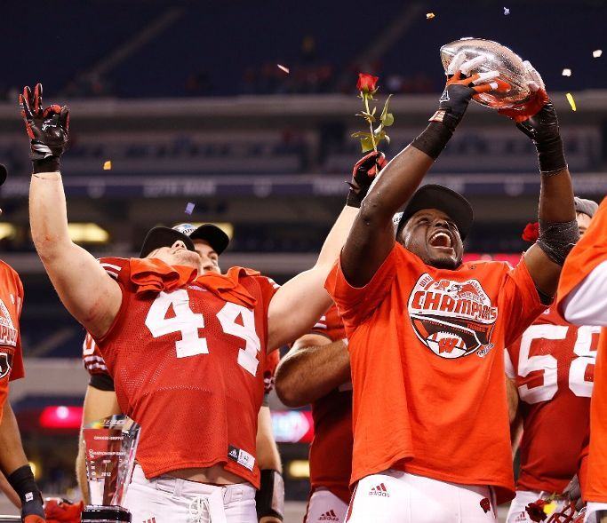 Montee Ball holds up the Stagg Championship Trophy with Chris Borland after beating the Nebraska Cornhuskers in the Big 10 Championship Game (Photo by Gregory Shamus/Getty Images)