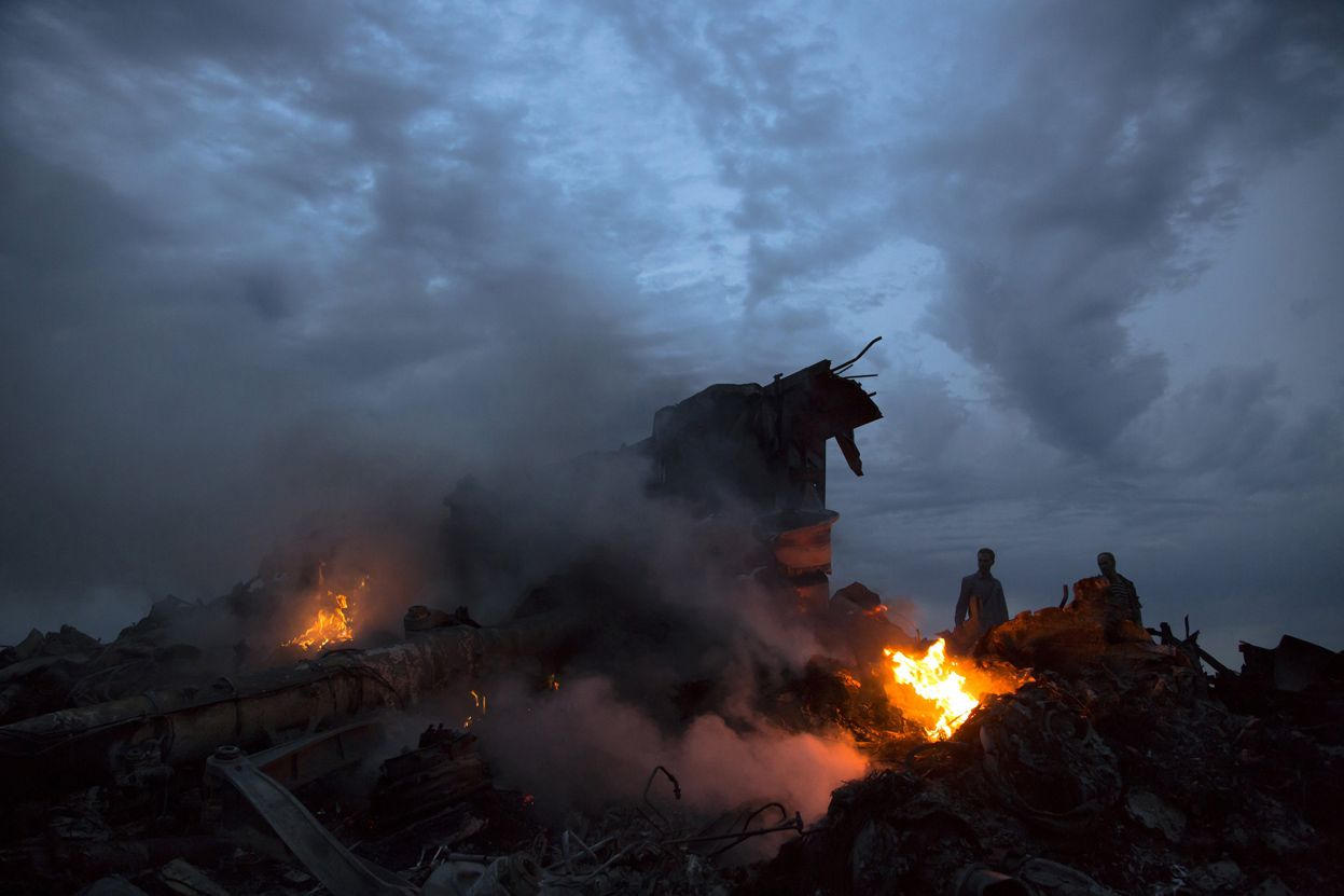 People walk yhrough the crash site of the Malaysia Airlines plane near the village of Hrabove, Ukraine, on July 17, 2014. (AP Photo/Dmitry Lovetsky)