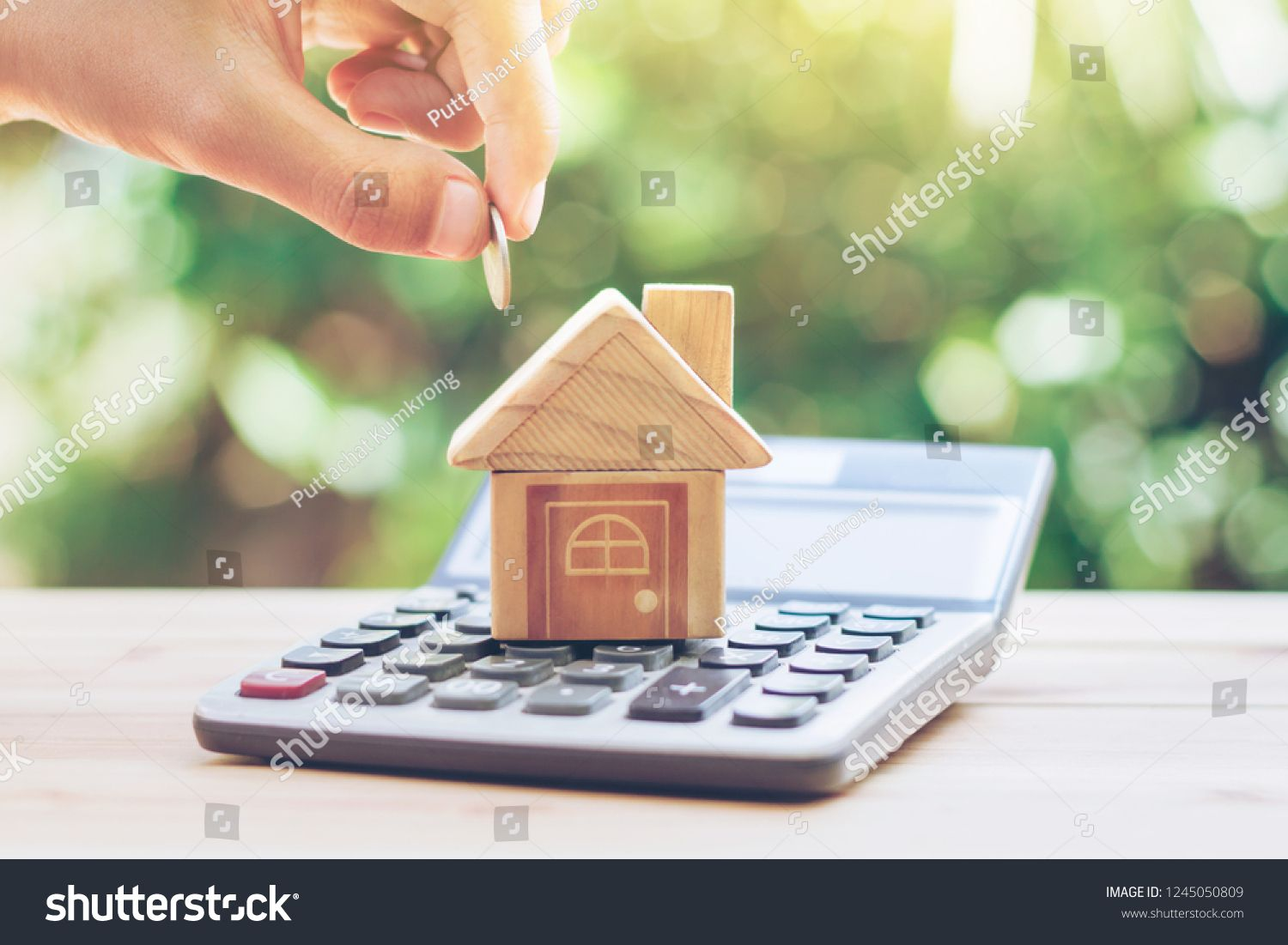 House Is Placed On The Calculator Hand That Is Coin Down The