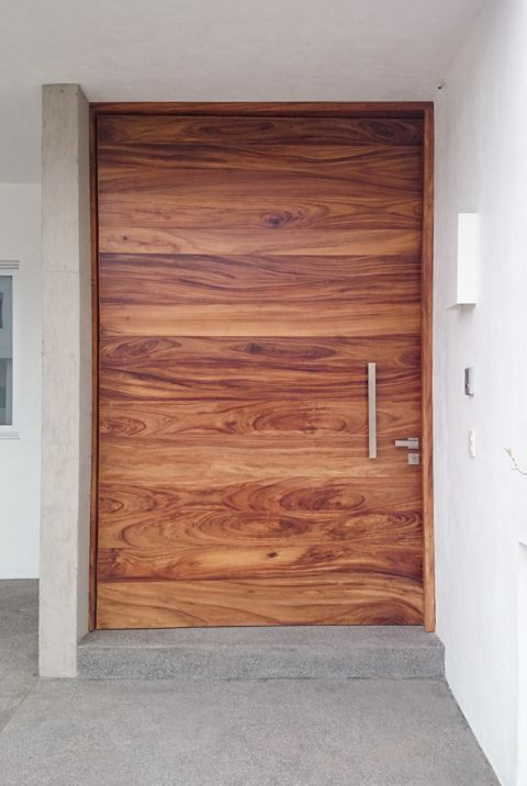 This gorgeous natural wood pivot door pops against the for Design your own front door