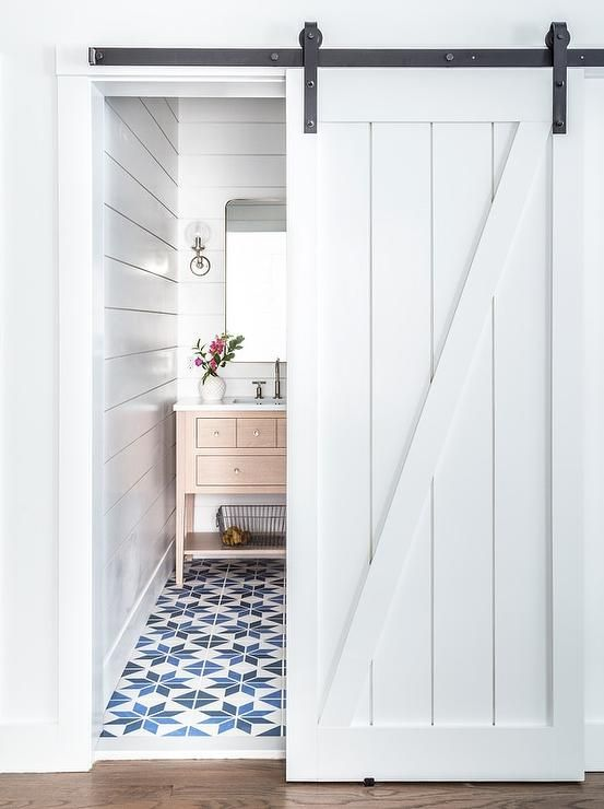 A White Shiplap Door Slides Open To A Reveal A Blue And